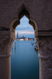 Beautiful view of magnificent building and calm water of channel behind ornamental stone arch in cloudy evening in Venice - ADSF02410