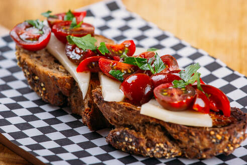 Close-up view of slice of rye bread with thin slices of cheese and halves of fresh cherry tomatoes placed on checkered board on wooden table - ADSF02569