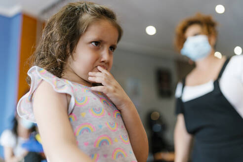 Upset girl looking away t hairdresser in hair salon during pandemic - EGAF00475