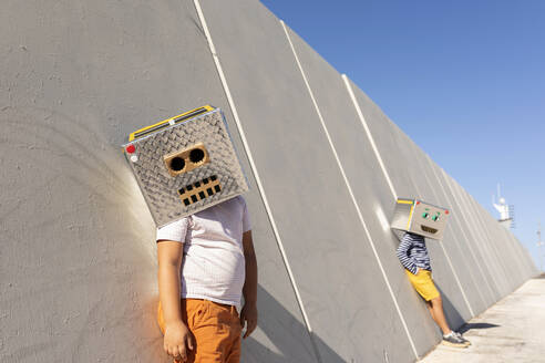 Boys wearing robot masks standing against wall in city on sunny day - VABF03132