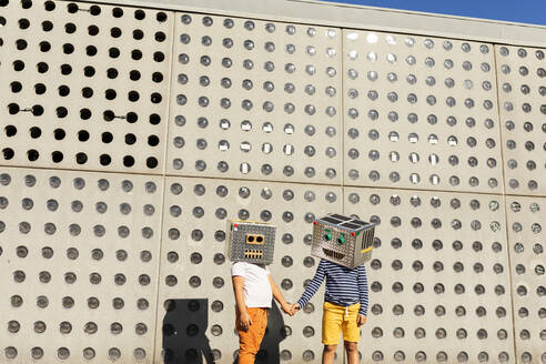 Friends wearing robot costumes holding hands while standing against wall on sunny day - VABF03141