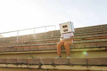 Boy wearing robot mask sitting on steps against sky during sunny day - VABF03147