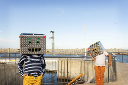 Boys wearing robot costumes standing on footpath against clear blue sky - VABF03150