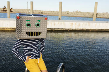 Boy wearing robot mask made of box while sitting by the water - VABF03153