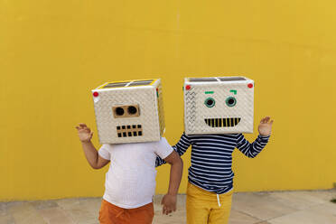 Friends wearing robot costumes waving while standing against yellow wall - VABF03156