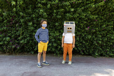 Boy in face mask standing with friend wearing robot costume against plants in park - VABF03162