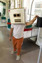 Boy wearing robot costume standing in train - VABF03165