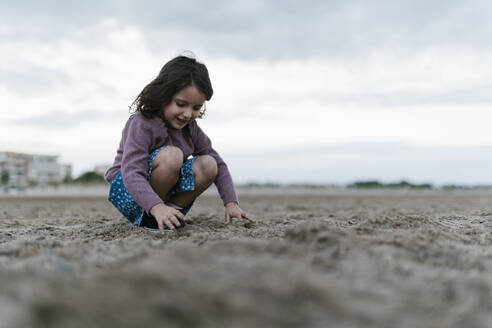 Smiling girl playing with sand while crouching at beach against cloudy sky - EGAF00477