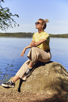 Mid adult woman wearing sunglasses sitting against lake in Tiveden National Park, Sweden - UKOF00013
