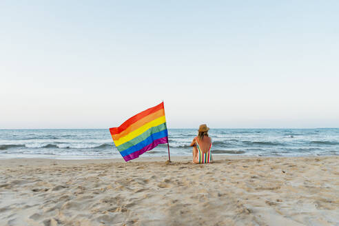 Marure woman sitting on the beach with gay pride flag - CJMF00315