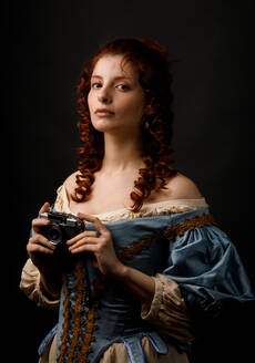 Beautiful female in lovely baroque dress holding photo camera and looking at camera while standing on black background - ADSF03573