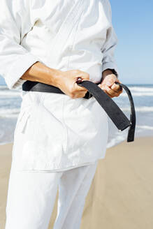 Close-up of mature man tying black belt while standing at beach - CJMF00317
