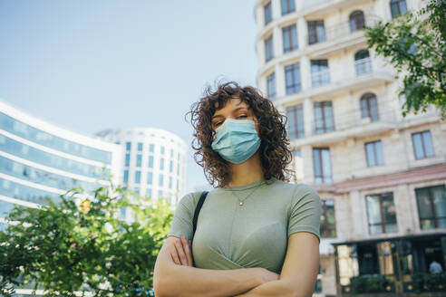 Brunette curly woman wearing protective mask in city - OYF00146