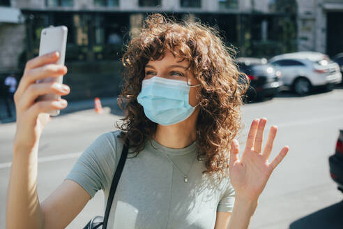 Woman wearing protective mask and using smartphone in city - OYF00149