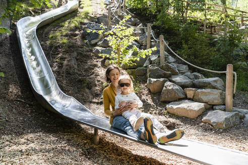 Mother with daughter playing on slide in forest - DIGF12755