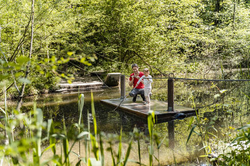 Father and daughter on wooden raft over lake in forest - DIGF12761