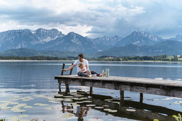 Father with daughter sitting on jetty over lake against mountains - DIGF12764