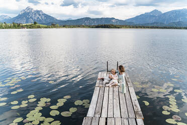 Mid adult woman and daughter sitting on jetty over lake against sky - DIGF12770