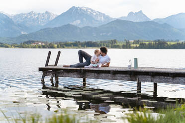 Father kissing daughter while sitting on jetty over lake against mountains - DIGF12773