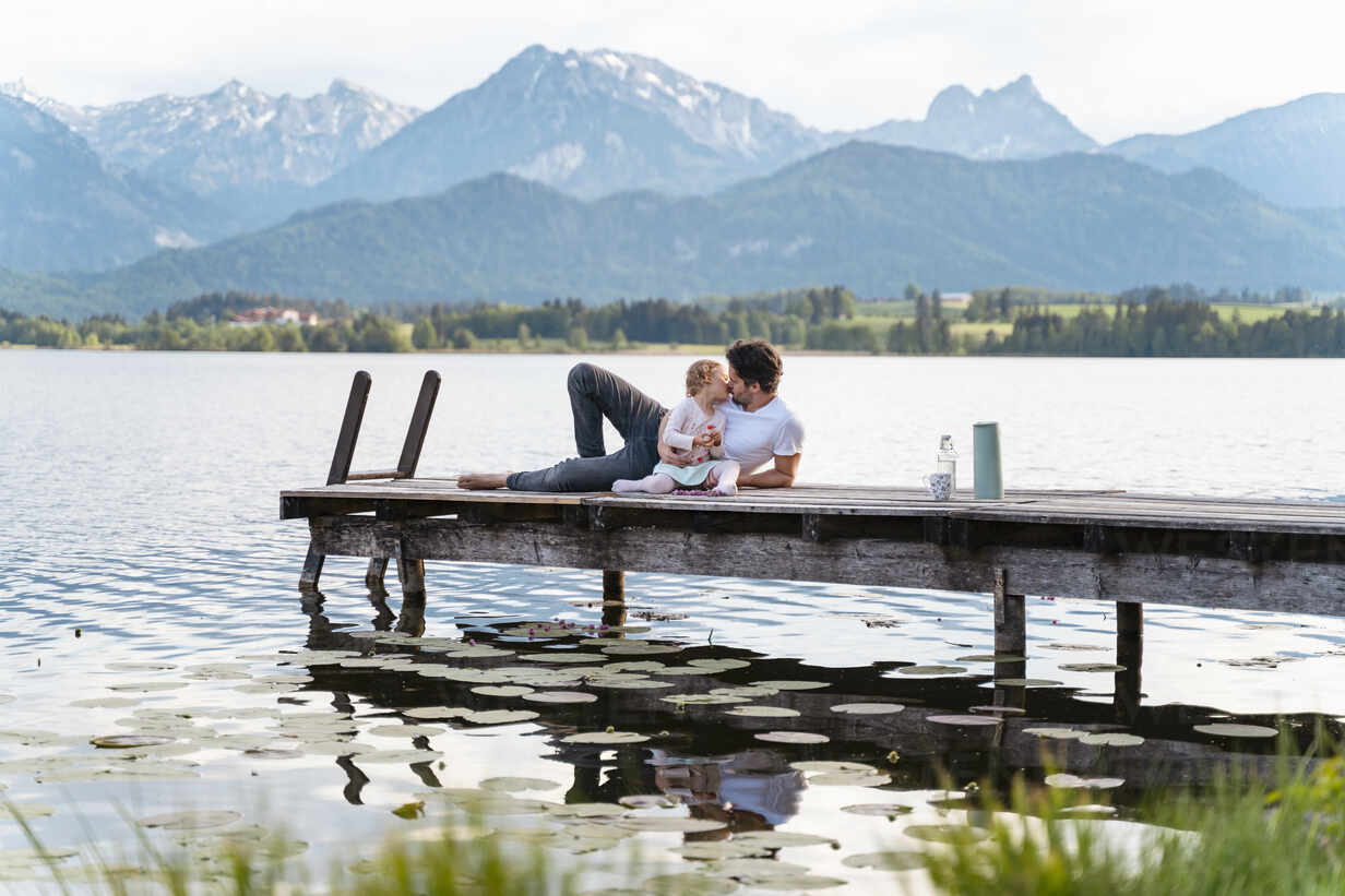 Father kissing daughter while sitting on jetty over lake against mountains - DIGF12773 - Daniel Ingold/Westend61
