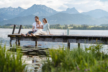 Happy family looking at view while sitting on jetty over lake against mountains - DIGF12776