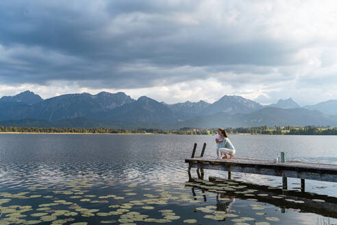 Mother with daughter looking at lake while crouching on jetty against cloudy sky - DIGF12779
