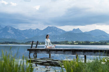 Mid adult woman meditating on jetty over lake against cloudy sky - DIGF12788