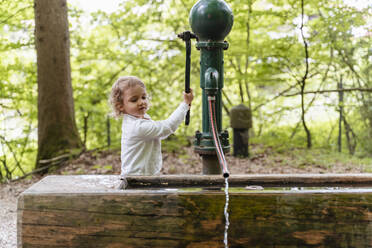 Cute girl playing with fountain against trees in forest - DIGF12791