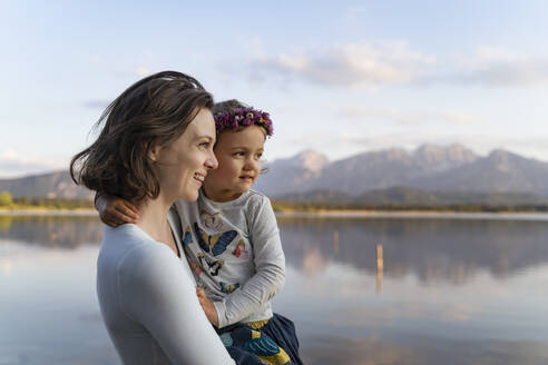 Smiling mother carrying cute daughter while standing against lake at sunset - DIGF12797