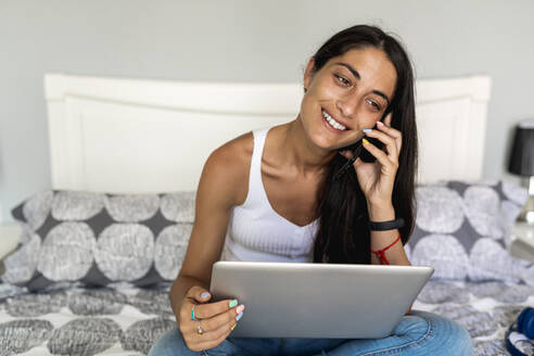 Smiling woman talking over smart phone while sitting with laptop on bed at home - EGAF00530