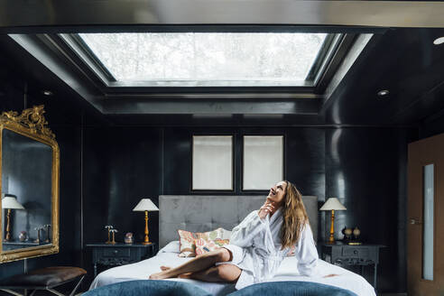 Mid adult woman looking through skylight while relaxing on bed in hotel - OCMF01547