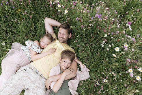 Smiling father with children lying on land amidst flowers - EYAF01220