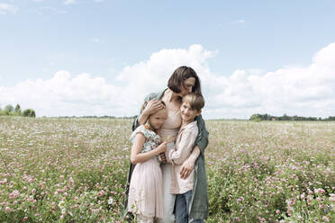 Loving mother embracing children while standing amidst flowers in field against sky - EYAF01223