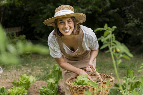 Smiling young woman wearing hat collecting vegetables in wicker basket at yard - AFVF06830