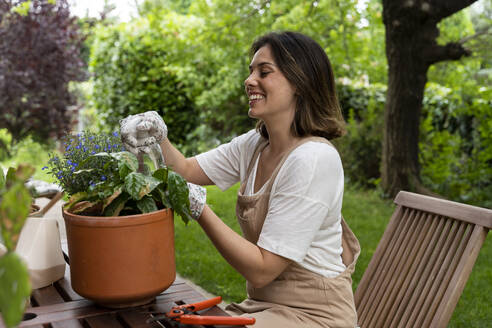 Cheerful woman with potted plant on table sitting in yard during curfew - AFVF06839