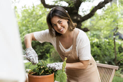 Smiling young woman taking care of plants in yard during curfew - AFVF06842