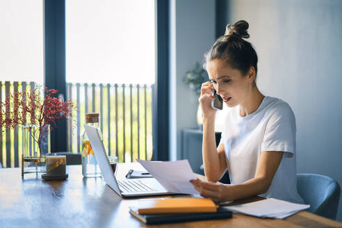 Businesswoman holding document talking over smart phone at desk in home office - BSZF01580