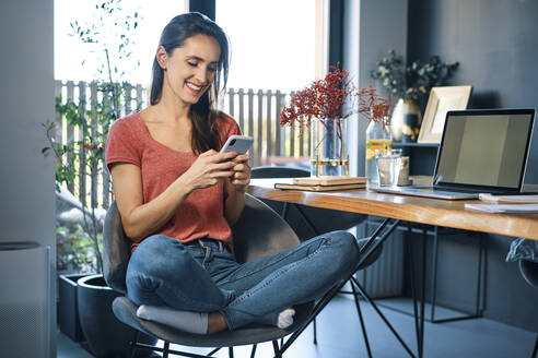 Female entrepreneur using smart phone while sitting on chair by desk in home office - BSZF01592