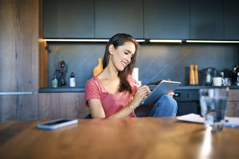 Smiling female entrepreneur using digital tablet while sitting at desk in home office - BSZF01604