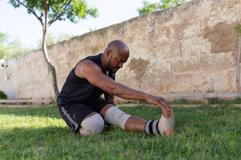 Mature man with shaved head exercising on grassy land against wall in yard - JPTF00568