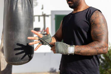 Close-up of man tying bandage on hand while standing by punching bag in yard - JPTF00574