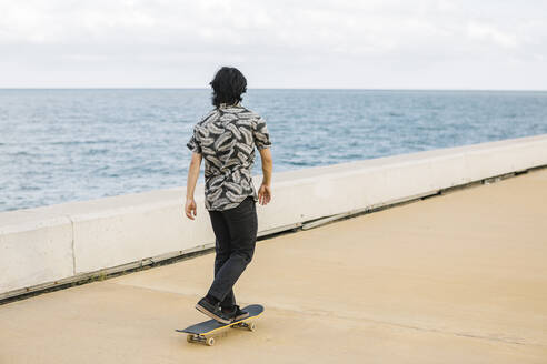 Young man skateboarding on promenade by sea in city - XLGF00393