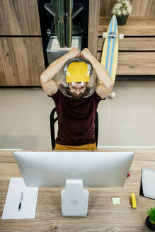 Tensed businessman wearing fishbowl while using computer in modern office - RCPF00240
