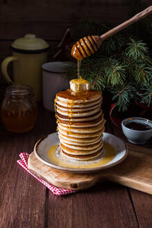 Stack of tasty pancakes served with butter and honey on wooden table. - ADSF05281