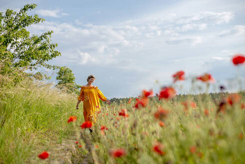 Happy mature woman walking amidst poppy field against sky - BFRF02270