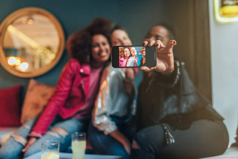 Group of three beautiful young multiracial women sitting in a coffee shop taking a selfie on the mobile phone - ADSF05811