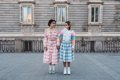 Two young women with theatrical makeup and unusual clothes performing on city street - ADSF06130