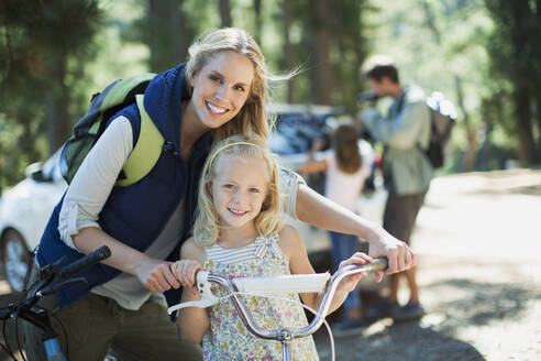 Smiling mother and daughter with bicycle in woods - CAIF28516