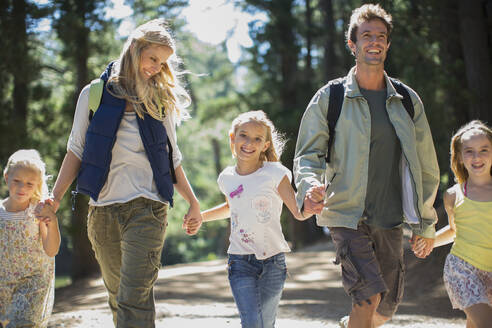 Smiling family holding hands and walking in woods - CAIF28567
