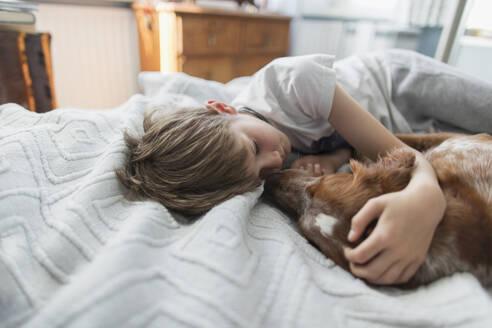Cute boy cuddling dog on bed - CAIF28807